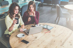 Zwei junge Frauen sitzen am runden Holztisch im Café, trinkender Kaffee und betrachten Laptopschirm Stockbilder