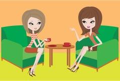 Zwei junge Frauen sprechen in den Lehnsesseln Stockfotografie