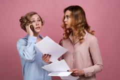 Zwei junge Frauen studieren Papierwertpapiere in ihren Händen vor ihnen Eins von ihnen rät am Telefon stockbilder