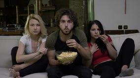 Zwei junge Frauen und ein Kerl, der Popcorn isst und Horrorfilm mit der Furcht grimmig auf ihrem Gesicht aufpasst stock video footage