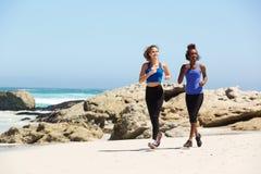 Zwei junge Frauen in voller Länge, die auf dem Strand laufen Lizenzfreies Stockbild
