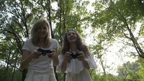 Zwei junge Frauen, welche die Videospiele im Freien mit Gamerkonsolensteuerknüppel spielen - stock footage