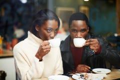 Zwei junge Freunde, die Schalen halten, trinken Kaffee im Café Lizenzfreies Stockfoto