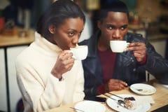 Zwei junge Freunde, die Schalen halten, trinken Kaffee im Café Stockbilder