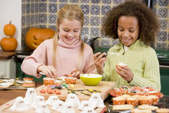 Zwei junge Freundinnen bei Halloween in der Küche Lizenzfreie Stockfotos
