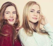 Zwei junge Freundinnen in den Winterstrickjacken, die zuhause Spaß haben lebensstil Blonde jugendlich Freunde schließen oben Stockbild