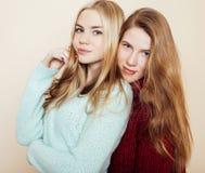 Zwei junge Freundinnen in den Winterstrickjacken, die zuhause Spaß haben lebensstil Blonde jugendlich Freunde schließen oben Stockfotografie