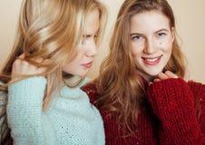 Zwei junge Freundinnen in den Winterstrickjacken, die zuhause Spaß haben lebensstil Blonde jugendlich Freunde schließen oben Lizenzfreies Stockfoto