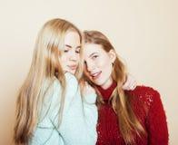 Zwei junge Freundinnen in den Winterstrickjacken, die zuhause Spaß haben lebensstil Blonde jugendlich Freunde schließen oben Lizenzfreies Stockbild
