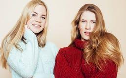 Zwei junge Freundinnen in den Winterstrickjacken, die zuhause Spaß haben lebensstil Blonde jugendlich Freunde schließen oben Stockfotos
