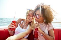 Zwei junge Freundinnen, die auf einem Boot mit Getränken sich entspannen lizenzfreies stockbild