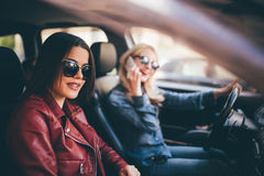 Zwei junge Freundinnen, die zusammen im O-Auto sprechen, während sie auf eine Autoreise gehen, während Fahrer am Telefon sprechen Lizenzfreie Stockfotos