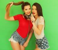Zwei junge Freundinnen, die zusammen stehen und Spaß haben Stockfotografie