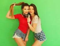 Zwei junge Freundinnen, die zusammen stehen und Spaß haben Lizenzfreies Stockfoto