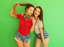 Zwei junge Freundinnen, die zusammen stehen und Spaß haben Stockbild