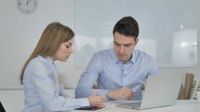 Zwei junge Geschäfts-Kollegen, die an Laptop arbeiten stock footage