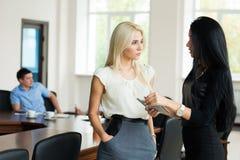 Zwei junge Geschäftsfrauen blond und Brunette mit einem Tablette compu Stockfotos