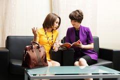 Zwei junge Geschäftsfrauen, die auf einer Couch sitzen Stockfotografie