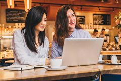 Zwei junge Geschäftsfrauen, die bei Tisch im Café sitzen und Laptop, Funktion, blogging verwenden Mädchen betrachten Monitor Lizenzfreies Stockbild