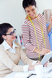 Zwei junge Geschäftsfrauen, die mit digitaler Tablette in ihr offic arbeiten Lizenzfreie Stockfotos