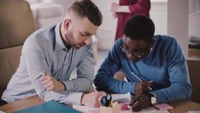 Zwei junge Geschäftskollegen arbeiten zusammen, zusammen schreibend auf Papierdiagramme durch die Tabelle beim multiethnischen Bü stock video