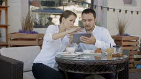 Zwei junge Geschäftsleute, die digitale Tablette auf einer Sitzung an der Kaffeestube verwenden stockfotografie