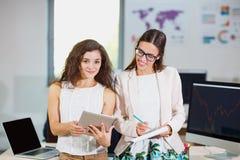 Zwei junge Geschäftsmädchen überprüfen Dokumente und eine Tablette stockfotografie