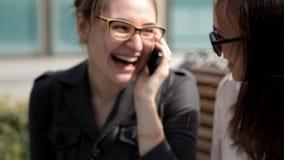 Zwei junge Geschäftsmädchen am Mittagessen, das im Park nahe dem Geschäftszentrum sitzt, am Telefon lacht und spricht stock video