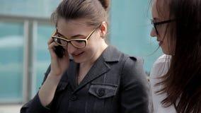 Zwei junge Geschäftsmädchen sitzen im Park nahe dem Geschäftszentrum und sprechen am Telefon mit Geschäftsleuten Geschäft stock footage