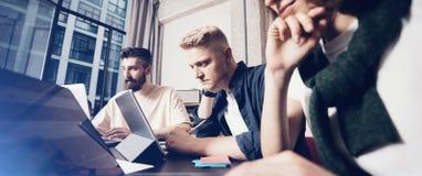 Zwei junge Geschäftsmänner, die über Geschäft während einer von ihnen Computermonitor zeigend sprechen Gruppe junge Mitarbeiterle lizenzfreie stockbilder