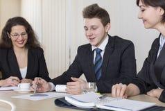 Zwei junge Geschäftsmänner, die über Geschäft während einer von ihnen lehnend auf den Computermonitoren sprechen Stockfotografie