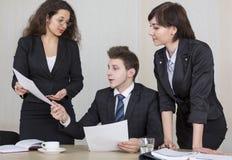 Zwei junge Geschäftsmänner, die über Geschäft während einer von ihnen lehnend auf den Computermonitoren sprechen Lizenzfreies Stockbild