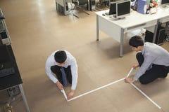 Zwei junge Geschäftsmänner, die herauf den Boden im Büro aufnehmen Lizenzfreie Stockfotos
