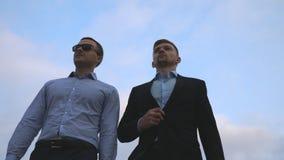Zwei junge Geschäftsmänner, die in Stadt mit blauem Himmel am Hintergrund gehen Geschäftsleute, die austauschen, um zusammenzuarb Stockbilder