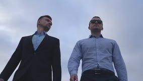 Zwei junge Geschäftsmänner, die in die Stadt mit blauem Himmel am Hintergrund gehen Hübsche Mitarbeiter, die austauschen, um zusa stock video