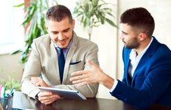 Zwei junge Geschäftsmänner unter Verwendung der Berührungsfläche bei der Sitzung Stockbild