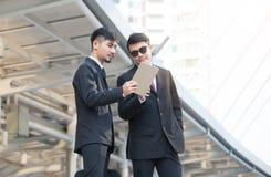Zwei junge Geschäftsmänner unter Verwendung einer digitalen Tablette zur Diskussion von proje Stockfotos