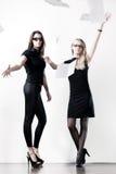 Zwei junge Geschäftsfrauen, die heraus Papier werfen Stockfotografie