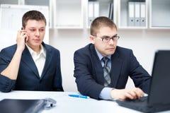 Zwei junge Geschäftsmänner, die im Büro zusammenarbeiten Stockfotografie