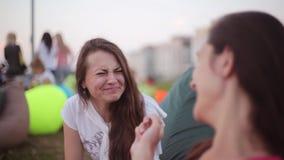 Zwei junge glückliche Brunettemädchen, die am Park sprechen Schöne Freunde, die am Sommertag lächeln und lachen stock video