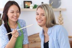 Zwei junge glückliche Frauen kochen in der Küche Freunde haben Spaß beim Preapering gesunde und geschmackvolle Mahlzeit Lizenzfreie Stockbilder