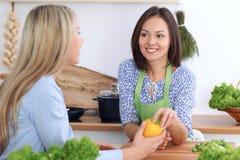 Zwei junge glückliche Frauen kochen in der Küche Freunde haben Spaß beim Preapering gesunde und geschmackvolle Mahlzeit Lizenzfreies Stockfoto
