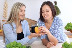 Zwei junge glückliche Frauen machen das on-line-Einkaufen durch Tablet-Computer und Kreditkarte Freunde werden im Th kochen Lizenzfreie Stockfotos