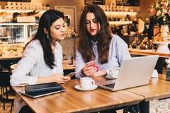Zwei junge glückliche Frauen sitzen im Café bei Tisch vor Laptop, unter Verwendung des Smartphone und des Lachens Lizenzfreies Stockfoto