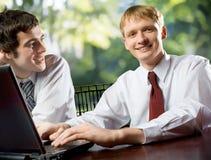 Zwei junge glückliche lächelnde Geschäftsleute oder Kursteilnehmer Lizenzfreies Stockfoto