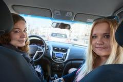 Zwei junge glückliche hübsche Frauen, die hinter dem Rad des Autos, zurück schauend sitzen Lizenzfreie Stockbilder