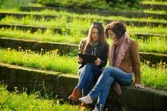 Zwei junge hübsche Frauen sitzen an den Steinschritten mit der Tablette in den Händen Stockfotografie
