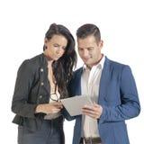 Zwei junge hübsche Geschäftsleute, die mit digitaler Tablette arbeiten Lizenzfreies Stockfoto