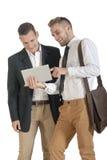 Zwei junge hübsche Geschäftsmänner, die mit digitaler Tablette arbeiten stockfotografie