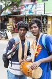 Zwei junge indische Männer, die Musikinstrumente Djembe beim Gehen in die Straße spielen stockfoto
